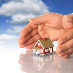 Hands and little house over sky background.